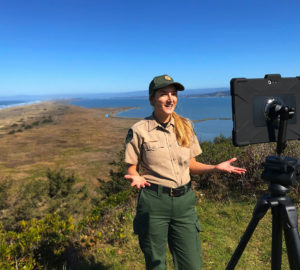 A female California State Parks naturalist interpreter in park ranger fatigues gives her presentation before a tablet on a tripod on which she is livestreaming a virtual program to Facebook.