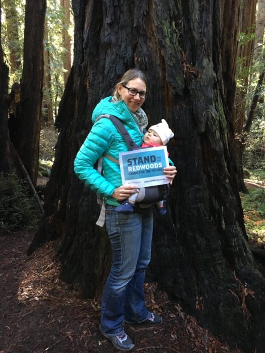 A woman wearing a turquoise puffer jacket and eyeglasses, holding a baby in front of a coast redwood tree.