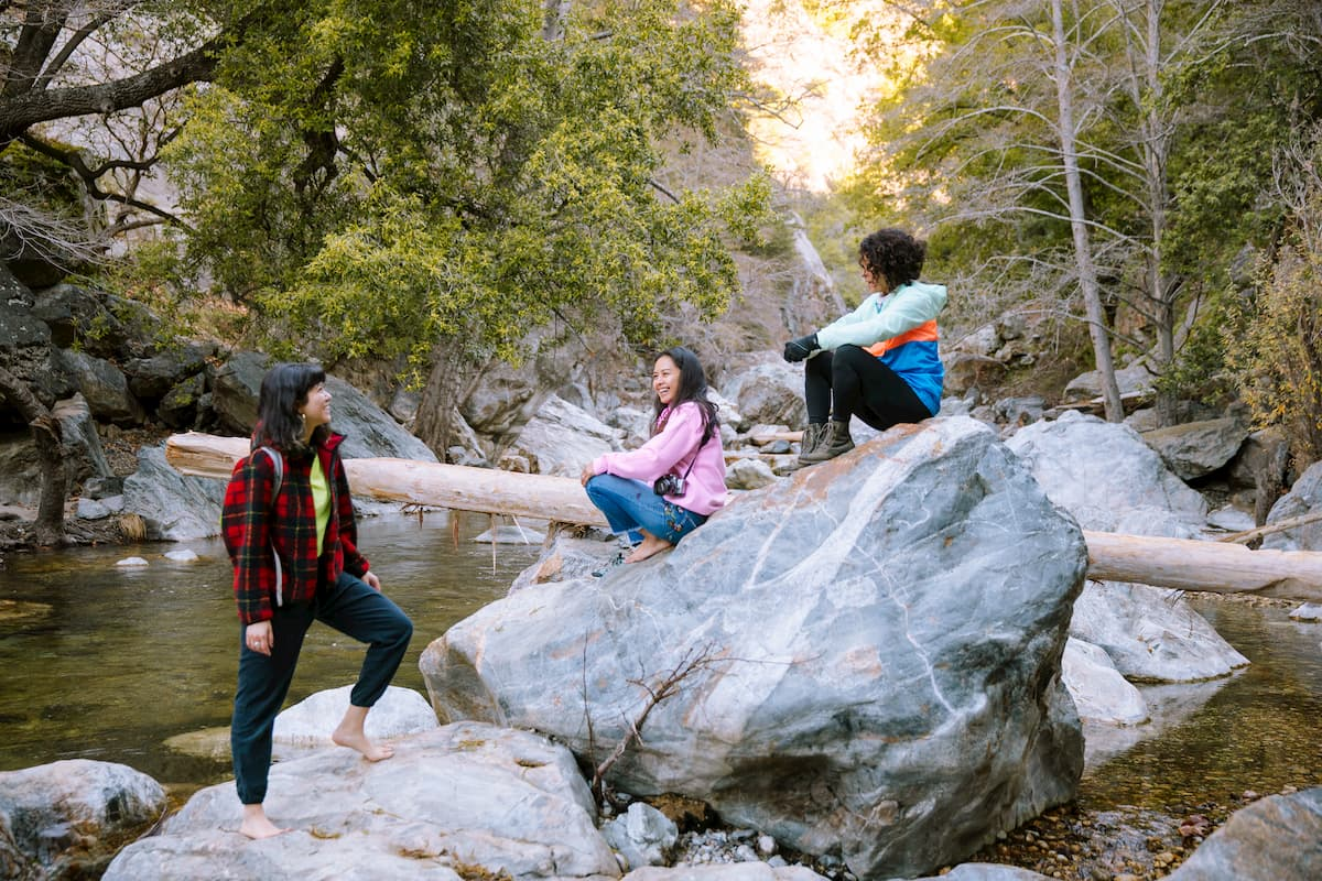 Three women of color smile and laugh with each other as they sit on a boulder in a creek in a redwood forest.