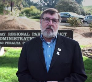 A man with a beard and glasses standing in front of a park sign with a car in the background