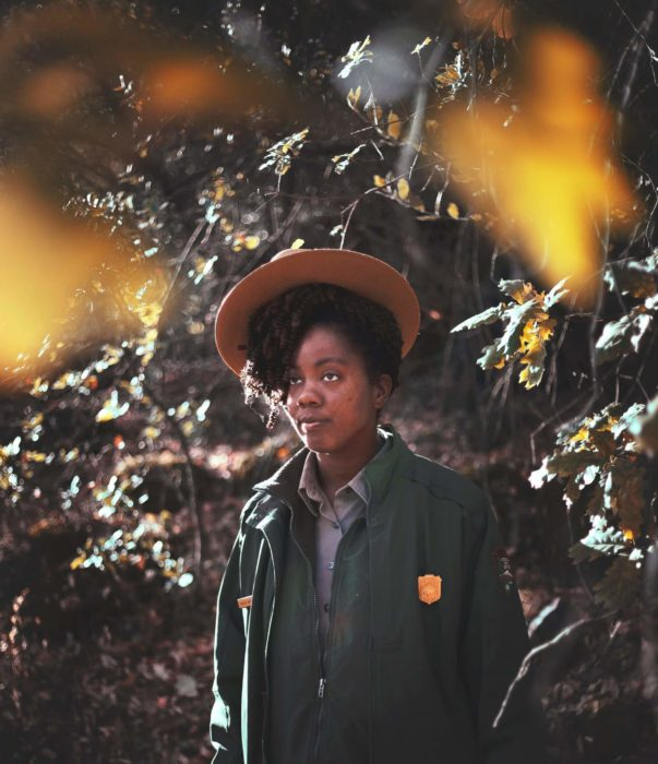 Image of a Black woman National Park Service ranger in uniform framed by yellow foliage in the foreground and foliage in the background