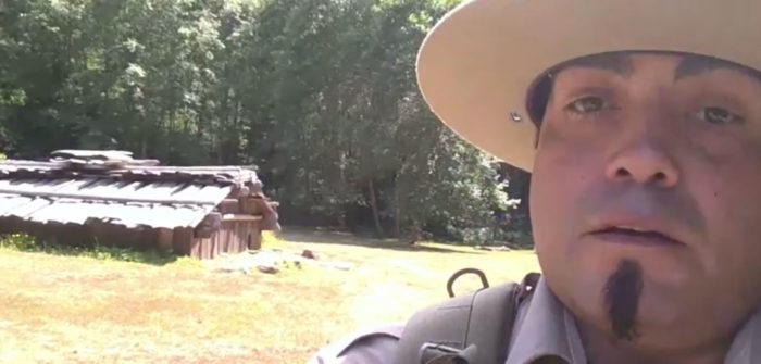 A close-up still frame of naturalist interpreter Skip Lowry, in his ranger fatigues, out in the field presenting a livestream naturalist program.