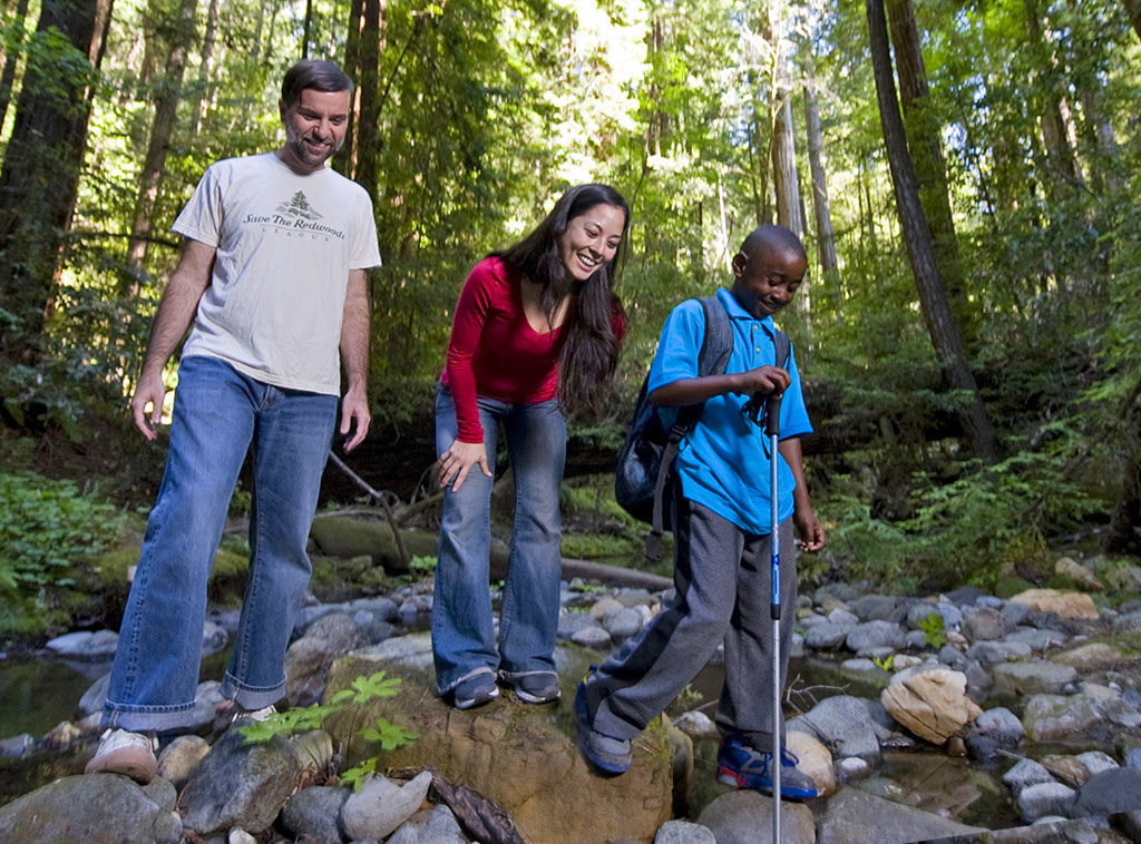 man, woman and kid hiking in the redwoods